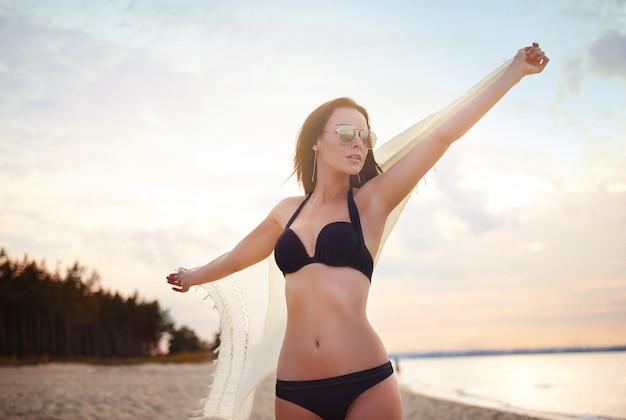 Mujer hermosa joven divirtiéndose en la playa