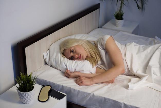 Mujer hermosa joven en el dormitorio de casa acostado en la cama tarde en la noche tratando de dormir sufriendo insomnio