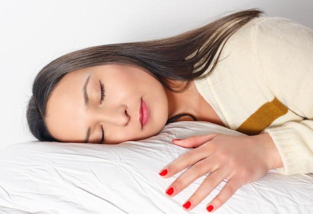 Mujer hermosa joven está durmiendo con la cabeza y la mano sobre la almohada. sueño saludable.
