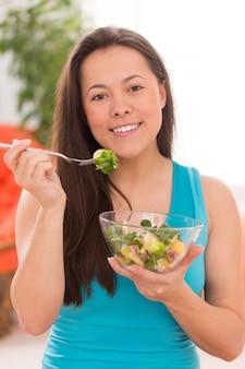Mujer hermosa joven con ensalada