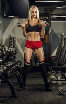 Mujer hermosa joven entrenando en el gimnasio.