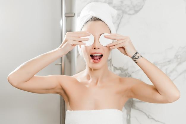 Mujer hermosa joven envuelta en toallas en el baño aplica almohadillas de algodón en los ojos