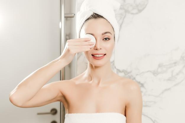 La mujer hermosa joven envuelta en toallas limpia su cara con el cojín de algodón en el cuarto de baño