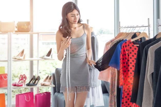 La mujer hermosa joven es sastre y diseñador. señora en hacer compras y elegir la ropa en tienda