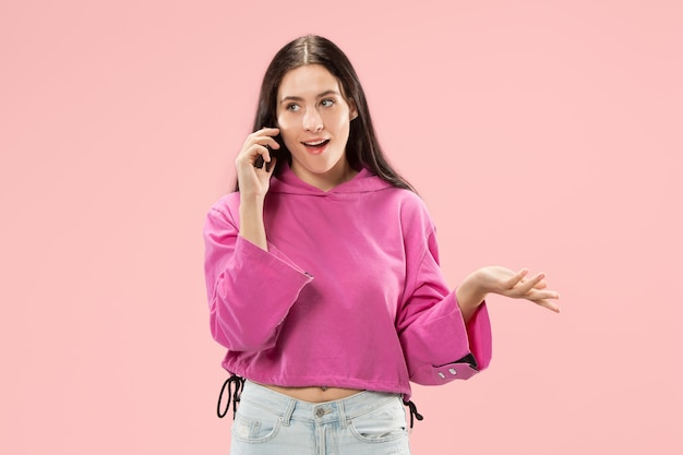 Mujer hermosa joven con estudio de teléfono móvil en la pared del estudio de color rosa