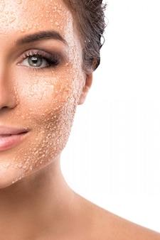 Mujer hermosa joven con exfoliante de azúcar en la cara