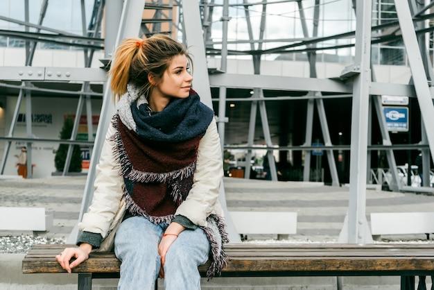 Mujer hermosa joven con exuberante cabello rubio en una bufanda se sienta en un banco en la ciudad, mira hacia arriba