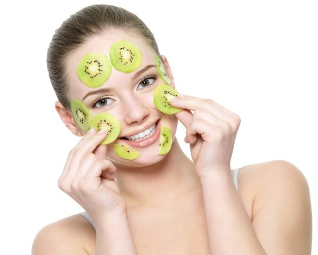 Mujer hermosa joven feliz con una máscara de kiwi de frutas en un rostro aislado en blanco