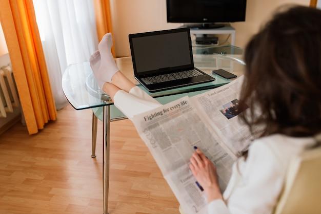 Mujer hermosa joven feliz trabaja usando la computadora portátil, en el interior