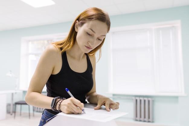 Mujer hermosa joven firmando documentos comerciales en el interior.