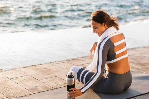 Mujer hermosa joven fitness sentado con toalla y agua