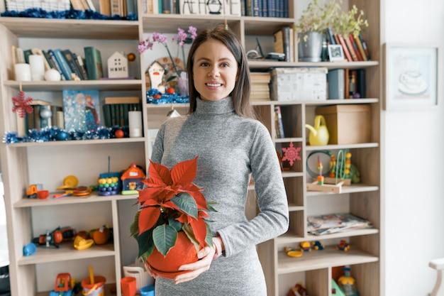 Mujer hermosa joven con flor de navidad roja flor de pascua