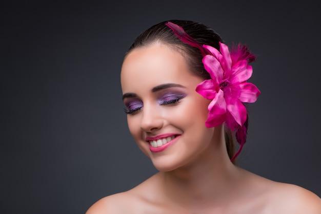 Mujer hermosa joven con la flor de la orquídea