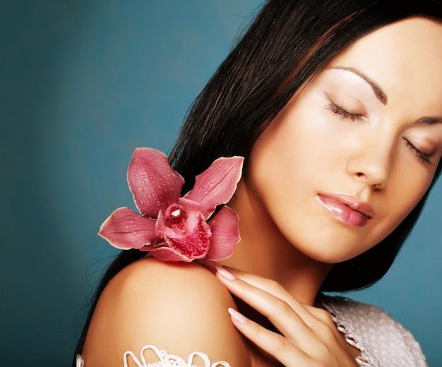 Mujer hermosa joven con flor rosa