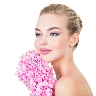 Mujer hermosa joven con flores junto a la cara.