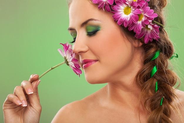 Mujer hermosa joven con flores en el pelo