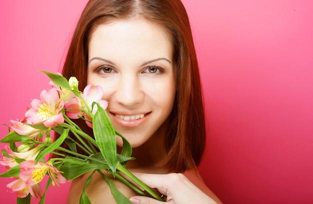 Mujer hermosa joven con flores rosas