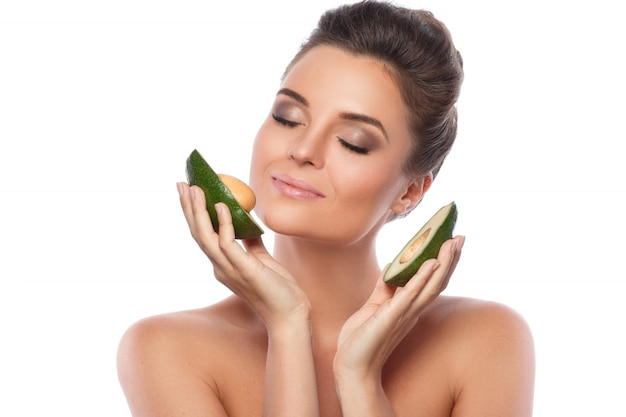 Mujer hermosa joven con fruta de aguacate