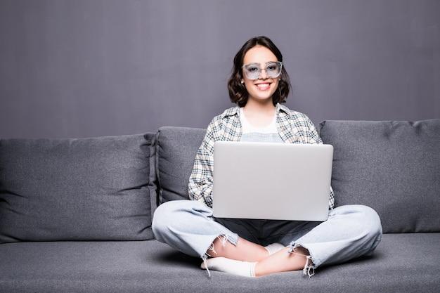 Mujer hermosa joven con gafas usando una computadora portátil en casa sentado en el sofá