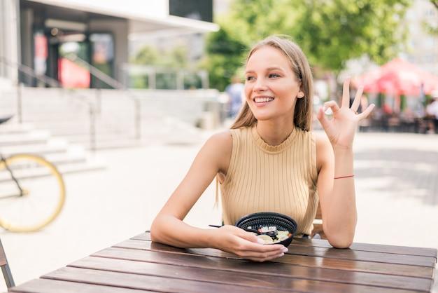 Mujer hermosa joven con gesto bien mientras come ensalada en el café al aire libre