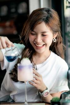 La mujer hermosa joven goza el comer del postre en el café