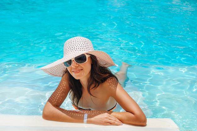 Mujer hermosa joven en gran sombrero blanco en el borde de la piscina
