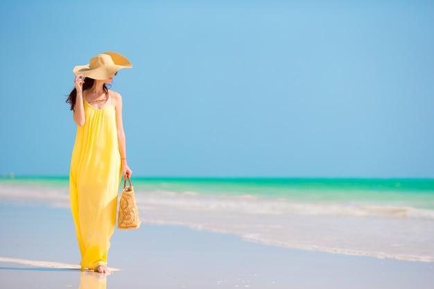 Mujer hermosa joven en gran sombrero durante vacaciones en la playa tropical