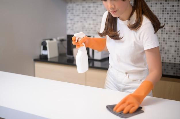 Una mujer hermosa joven con guantes de goma protectores está limpiando la mesa en la cocina de su casa.