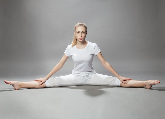 Mujer hermosa joven hace ejercicios en gris