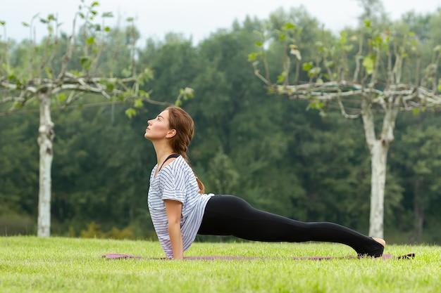 Mujer hermosa joven haciendo ejercicio de yoga al aire libre