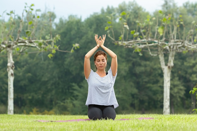 Mujer hermosa joven haciendo ejercicio de yoga en el parque verde