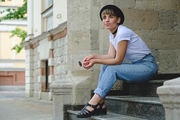 Mujer hermosa joven inconformista posando sentada en las escaleras