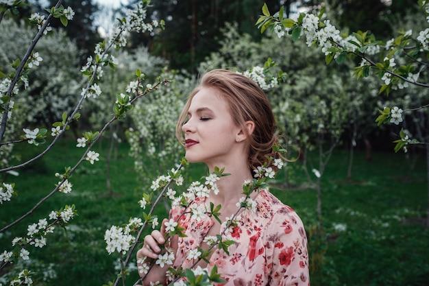 Mujer hermosa joven en el jardín de cerezos en flor.