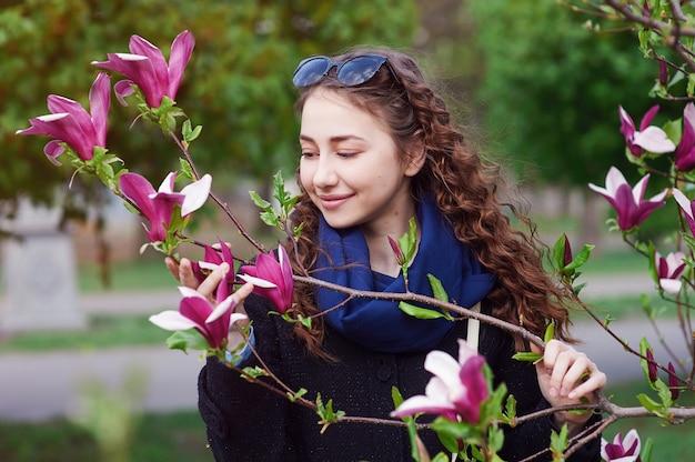 Mujer hermosa joven en el jardín floreciente