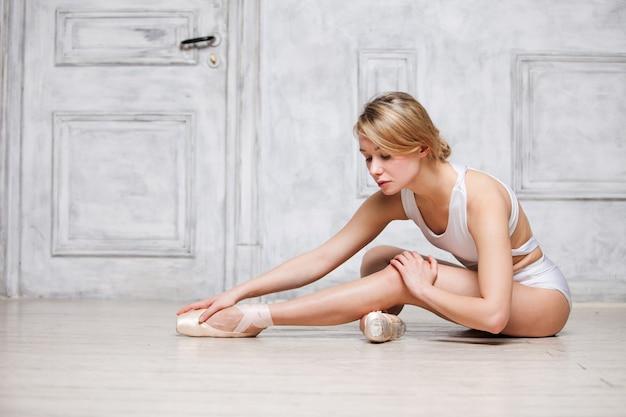 Mujer hermosa joven en leotardo de baile blanco y zapatos de punta