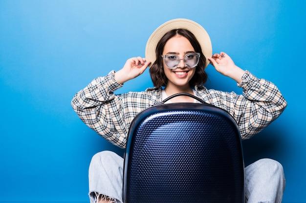 Mujer hermosa joven con maleta con gafas de sol y sombrero de paja listo para viaje de verano