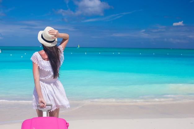Mujer hermosa joven con maleta grande en playa tropical