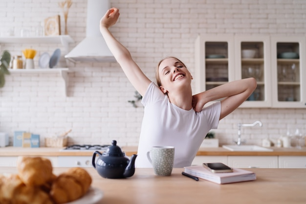 Mujer hermosa joven en la mañana en la cocina con té, estiramiento