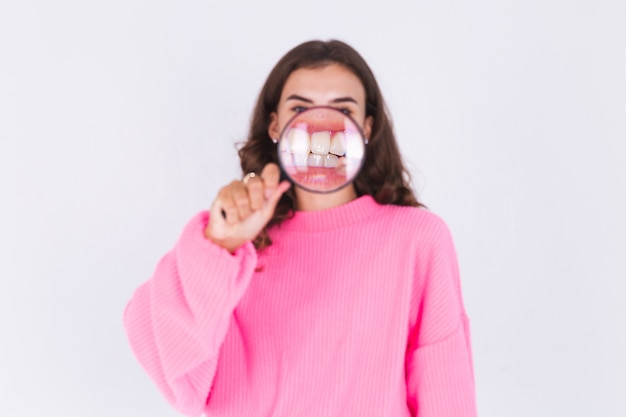 Mujer hermosa joven con maquillaje ligero pecas en suéter en la pared blanca con lupa muestra una sonrisa perfecta de dientes blancos