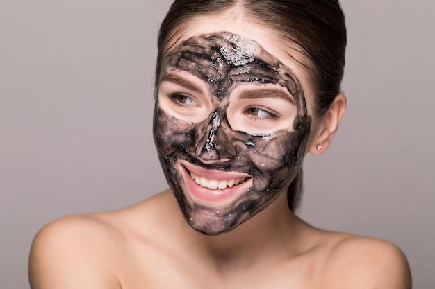 Mujer hermosa joven en una máscara para la cara del barro negro terapéutico. tratamiento de spa