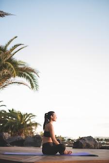 Mujer hermosa joven meditando al aire libre al amanecer.