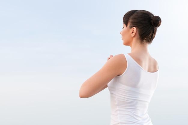 Mujer hermosa joven meditando al aire libre