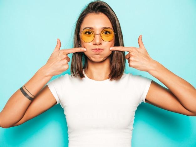 Mujer hermosa joven mirando a cámara. chica de moda en verano casual camiseta blanca y falda amarilla en gafas de sol redondas. la hembra positiva muestra emociones faciales. modelo divertido soplando sus mejillas.