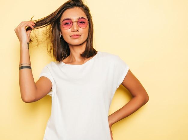 Mujer hermosa joven mirando a cámara. chica de moda en verano casual camiseta blanca y pantalones vaqueros en gafas de sol redondas. la hembra positiva muestra emociones faciales. modelo divertido aislado en amarillo