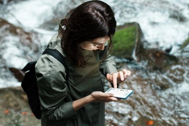Mujer hermosa joven con mochila mirando el teléfono