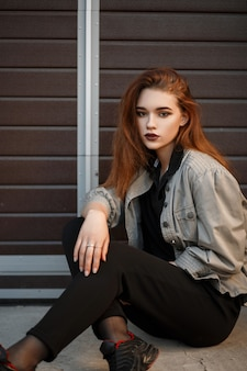 Mujer hermosa joven modelo en chaqueta de moda y camiseta negra con pantalones sentado en la calle cerca de la puerta