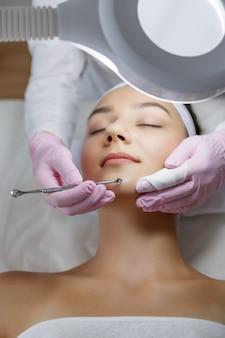 Mujer hermosa joven obtiene procedimiento de limpieza facial en un salón de belleza