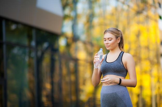 Mujer hermosa joven en el parque vistiendo ropa deportiva y agua potable