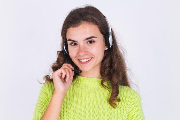 Mujer hermosa joven con pecas maquillaje ligero en suéter en la pared blanca con auriculares línea de ayuda trabajador call center manager sonrisa feliz