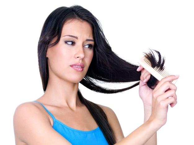 Mujer hermosa joven peinándose y mirando las puntas del cabello - aislado